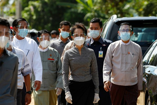 Aung San Suu Kyi, wearing a facemask and protective shield, walks with her advisers in Naypitaw.