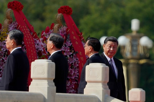 Chinese leader Xi Jinping, right, walks near the Monument to the People's Heroes during a ceremony
