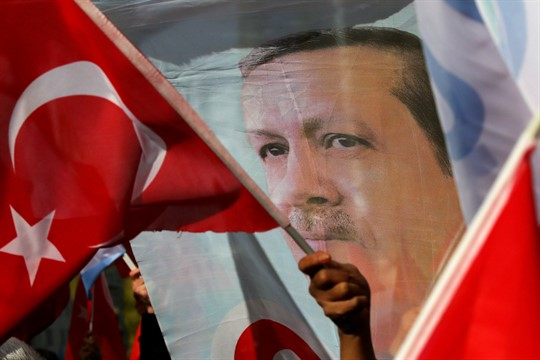 Demonstrators wave flags and a banner showing Turkish President Recep Tayyip Erdogan, in Brussels, Belgium