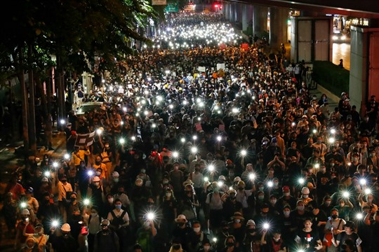 Pro-democracy demonstrators shine their mobile phone lights during a march in Bangkok