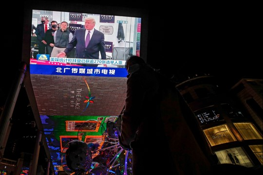 A giant TV screen shows an image of President Donald Trump during a newscast