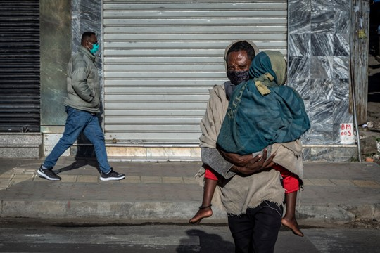 A man carries a child across a street in Addis Ababa, Ethiopia