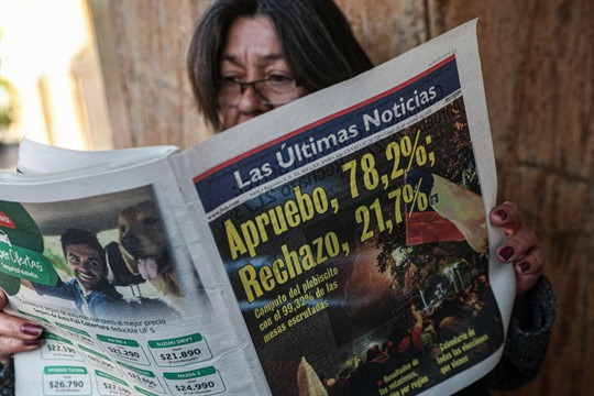 A woman reads a newspaper showing the results of the previous day's referendum, Santiago, Chile