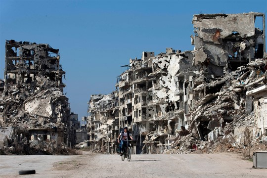 A Syrian boy rides a bicycle through a devastated part of the old city of Homs