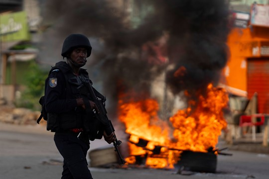 A policeman walks past a burning barricade during a protest in Abidjan, Cote d'Ivoire.
