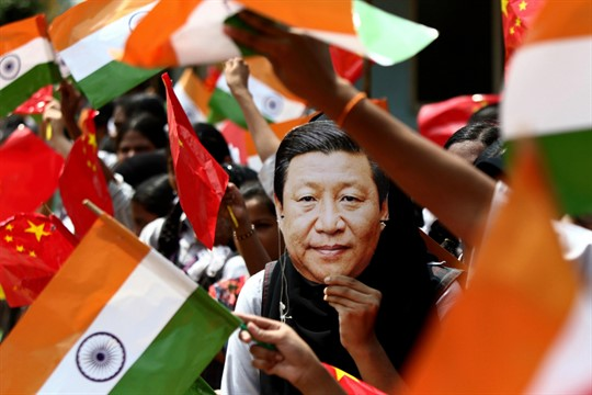 An Indian schoolgirl wears a mask of Chinese leader Xi Jinping