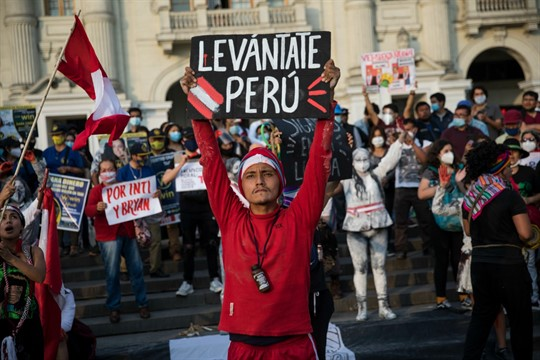 """A protester holds a sign that reads in Spanish, """"Wake up Peru,"""" during a protest"""