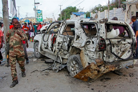A soldier walks past a wrecked vehicle outside the Elite Hotel in Mogadishu following al-Shabab's attack.