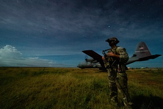 A U.S. Army sniper stands guard during a nighttime unloading operation in a field in Somalia