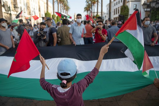 A young girl waves a Moroccan and a Palestinian flag during a protest