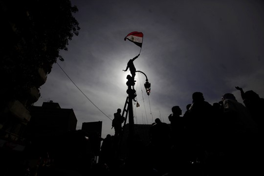 An Egyptian protester waves the national flag during a demonstration in Tahrir Square in 2012
