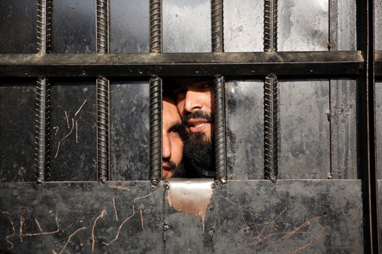 Taliban prisoners peer through the door of a Jalalabad prison after an ISIS-claimed attack