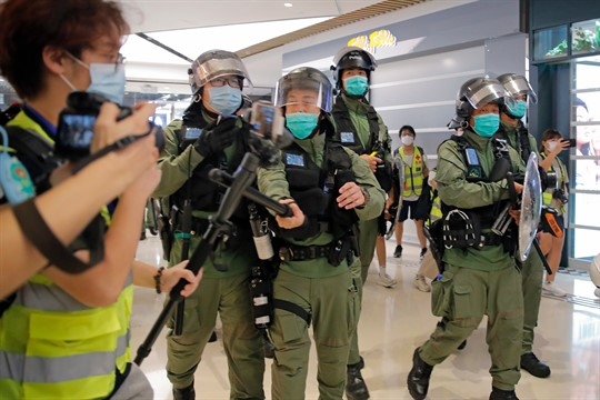 A police officer hits a journalist's microphone during a protest at a shopping mall, Hong Kong