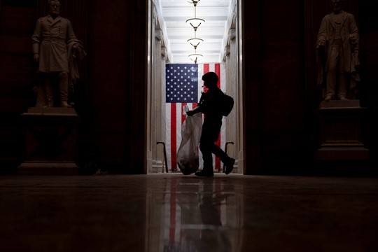 A police officer, silhouetted against the American flag, cleans up debris at the Capitol Rotunda.