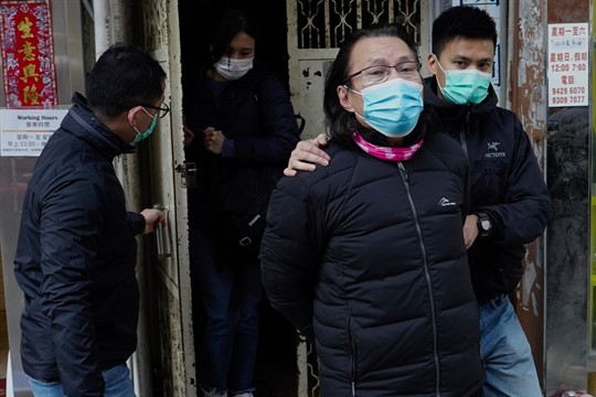 Lawyer Daniel Wong is escorted by police outside his office in Hong Kong