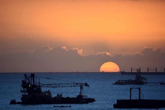 Oil rigs and ships silhouetted against the sunset in Claxton Bay, Trinidad and Tobago.