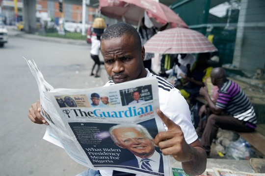 A man reads a newspaper reacting to the news of Joe Biden's election victory, in Lagos