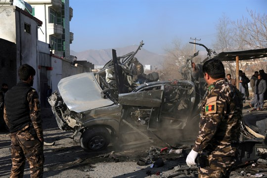 Afghan security personnel inspect the site of a bombing attack in Kabul, Afghanistan