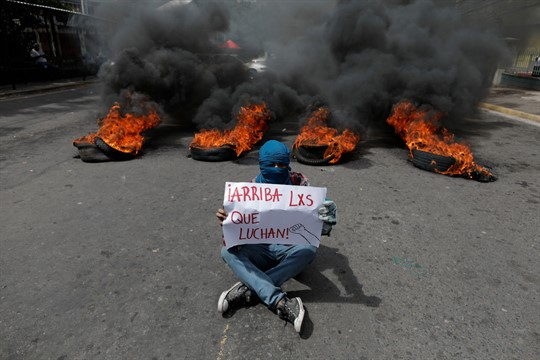 "A Honduran protester holds a sign that reads ""Hooray for those who fight,"" in Tegucigalpa"