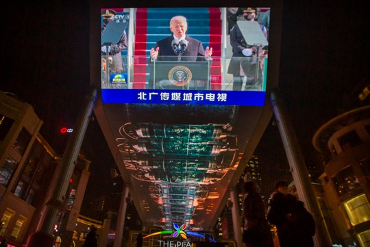 A large video screen shows a government news report about the inauguration of Biden, in Beijing