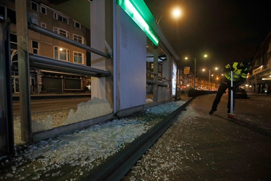 A police officer sweeps up glass after protests against a nationwide curfew in Rotterdam