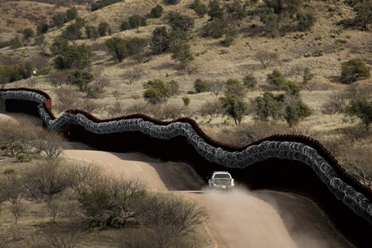 A Customs and Border Control agent patrolling on the U.S. side of the border with Mexico