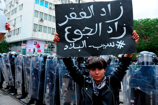 """A Tunisian demonstrator holds a sign reading, """"poverty rises, starvations rises"""" during a protest in Tunis."""