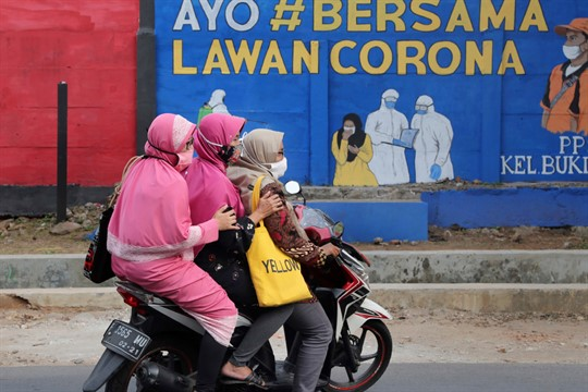 """Women ride past a coronavirus-themed mural reading """"Come on together fight the coronavirus,"""" in Jakarta, Indonesia"""