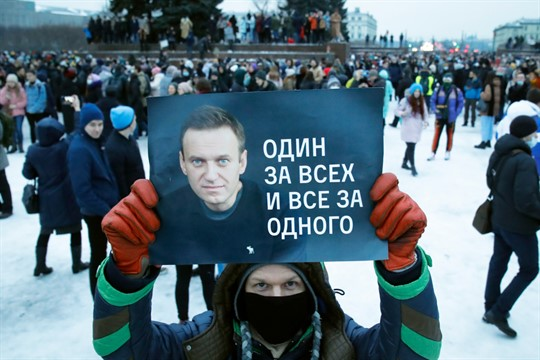 A man holds a poster of Alexei Navalny during a protest in St. Petersburg, Russia