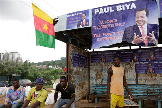 People sit under campaign election posters of President Paul Biya, in Yaounde, Cameroon