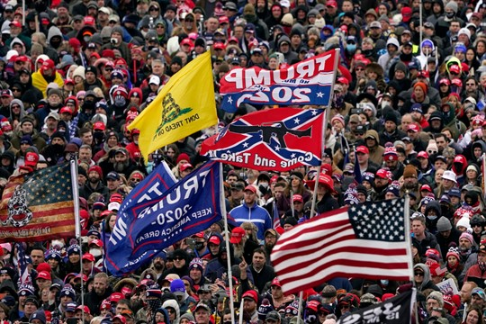 Supporters with Confederate-themed flags listen as Trump speaks during a rally in Washington