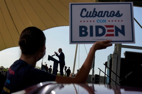"""A woman holds up a sign that reads, in Spanish, """"Cubans with Biden,"""