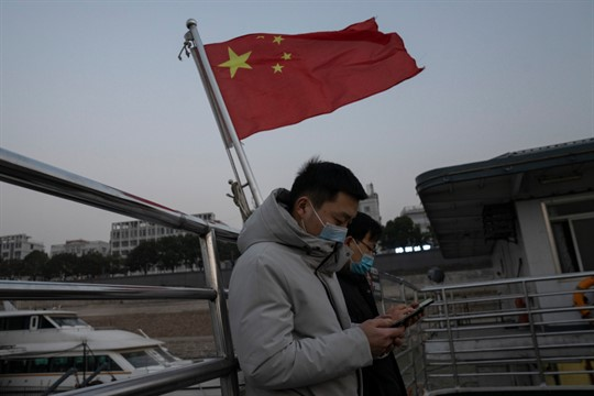 Residents taking the ferry stand near a Chinese national flag in Wuhan, China
