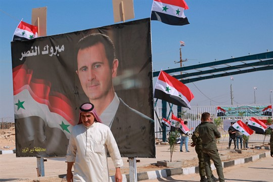 A poster of Assad with Arabic that reads,