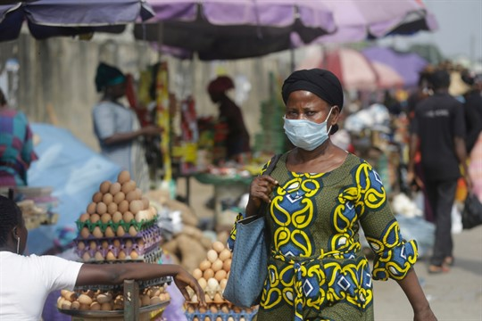 A woman wearing a face mask walks by a market in Lagos, Nigeria