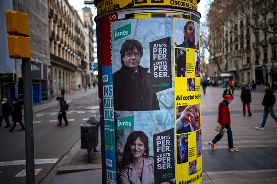 Posters show candidates for Catalonia's regional election, in Barcelona.