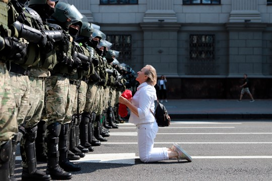 A woman kneels in front of riot police as they block Belarusian opposition supporters
