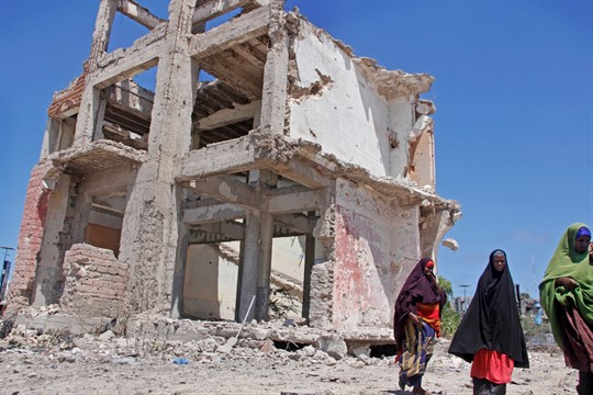 Somali women walk past a destroyed building after a suicide car bomb attack in Mogadishu