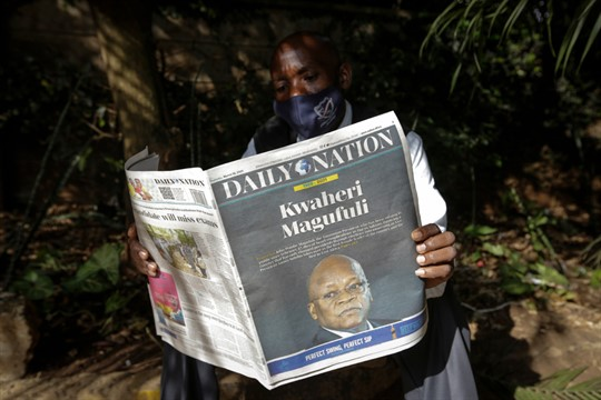 A man reads a copy of the Daily Nation newspaper reporting the death of John Magufuli