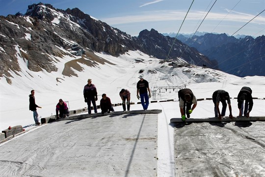 Workers cover a glacier with oversized plastic sheets on the peak of Germany's highest mountain, Zugspitze