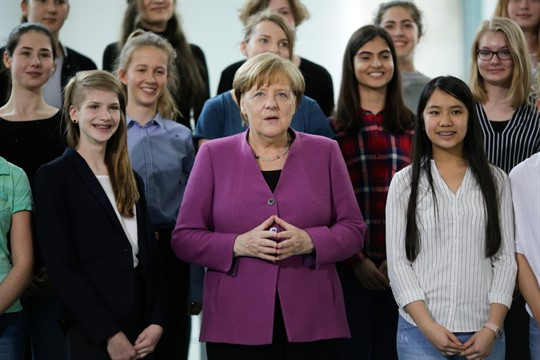 German Chancellor Angela Merkel with young women during an event at the chancellery in Berlin
