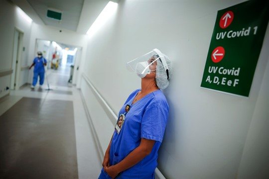 A health worker pauses in an ICU unit for COVID-19 patients in Porto Alegre, Brazil