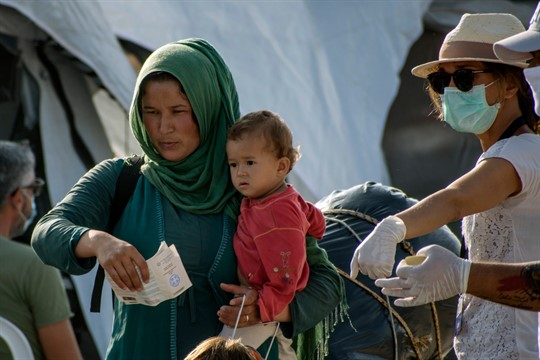 A woman with a baby entering a new temporary refugee camp, Lesbos, Greece