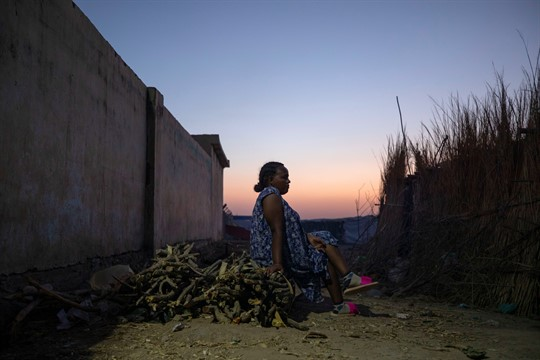 A Tigrayan refugee woman sits in front of her shelter near the Sudan-Ethiopia border.