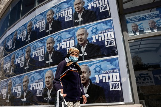 A woman passes Likud party campaign posters for Prime Minister Benjamin Netanyahu