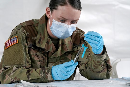 A U.S. Army medic fills syringes with the Johnson & Johnson COVID-19 vaccine