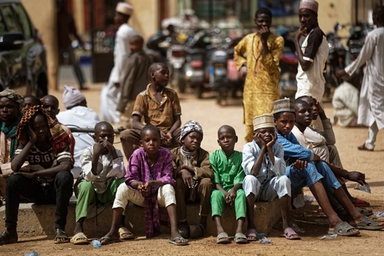 Young Muslim boys wait for traditional Friday prayers to begin at a mosque in Kano
