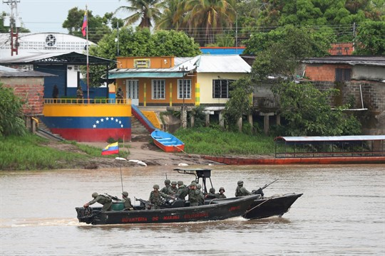 Venezuelan navy soldiers patrol the Arauca River, the natural border with Colombia, seen from Arauquita, Colombia