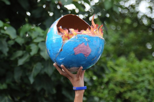 A girl holds a globe at a climate change protest in Mumbai, India