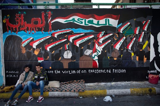 Two protesters sit by a mural showing Iraqi flags in Tahrir Square, Baghdad.